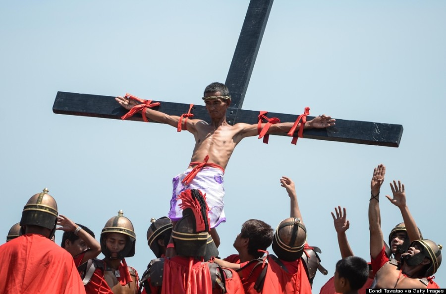 MANILA, PHILIPPINES - APRIL 18: A Catholic devotee nailed to a cross is hoisted by participants during a re-enacment of the crucifixion of Christ on Good Friday on April 18, 2014 in San Pedro Cutud village in Pampanga province, Philippines. At least 18 people were nailed to the cross including a Danish national in annual crucifixion rites in small villages in Pampanga. The annual event draws huge crowds of people to normally sleepy towns in northern Philippines. (Photo by Dondi Tawatao/Getty Images)