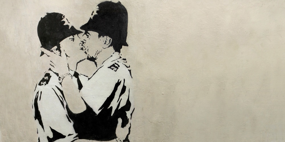 "This undated photo provided by Keszler Gallery in New York, Tuesday, Feb. 18, 2014, shows ""Kissing Coppers,"" a black-and-white stencil of two uniformed English ""bobbies"" (police officers) in a passionate clinch. The image was spray-painted in 2005 on the Prince Albert Pub in Brighton, England. Three works by the elusive British street artist Banksy, including two that had to be removed from the sides of buildings, are expected to bring hundreds of thousands of dollars Tuesday night at the Fine Art Auctions Miami. (AP Photo/ Keszler Gallery)"