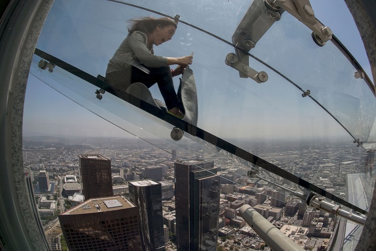 A woman slides down the Skyslide, a 45-foot outdoor glass slide 70 floors up on the outside of the US Bank Tower, on June 23, 2016 in Los Angeles, California, during a preview the opening of the attraction. / AFP PHOTO / DAVID MCNEW