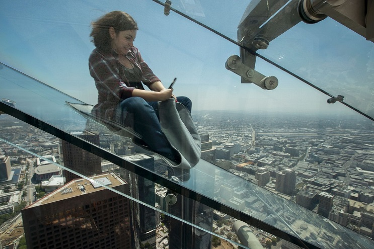 People slide down the Skyslide, a 45-foot (13.7-meter) glass slide 70 floors up on the outside of the US Bank Tower, on June 23, 2016 in Los Angeles, California, during a preview the opening of the attraction.  / AFP PHOTO / DAVID MCNEW