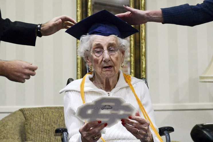 97-year-old Margaret Thome Bekema looks at her high school letter as Catholic Central High School principal Greg Deja, left, and Director of Advancement Beth Banta fix her cap shortly after her honorary graduation at Stonebridge Manor on Thursday, Oct. 29, 2015 in Grand Rapids, Mich.. Bekema began her education at Catholic Central in 1932 but sacrificed completing her degree at that time to take care of her mother who had cancer and her younger siblings. (Emily Rose Bennett/The Grand Rapids Press via AP) ALL LOCAL TELEVISION OUT; LOCAL TELEVISION INTERNET OUT; MANDATORY CREDIT (Emily Rose Bennett | MLive.com)