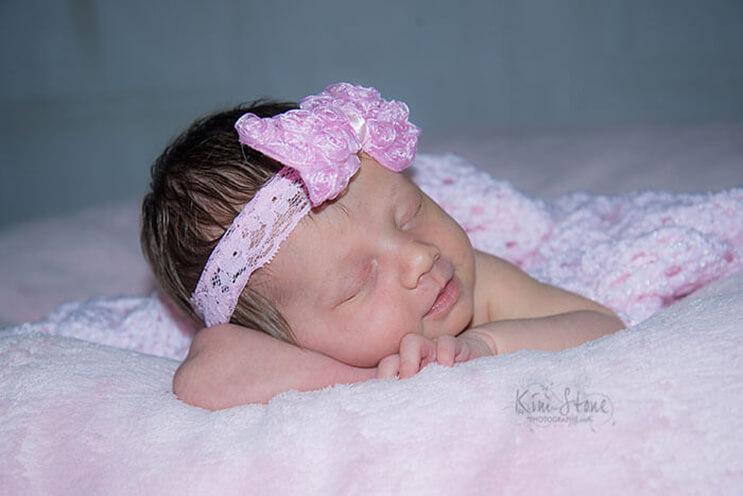 Recién nacida sonríe mientras duerme acurrucada en los guantes de su fallecido padre 03