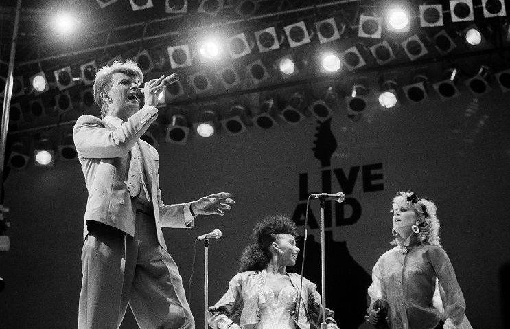 David Bowie performs on stage at London's Wembley Stadium during the Live Aid famine relief rock concert, July 13, 1985. (AP Photo/Joe Schaber)